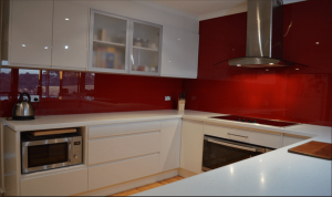 White based kitchen with red glass splashback installed